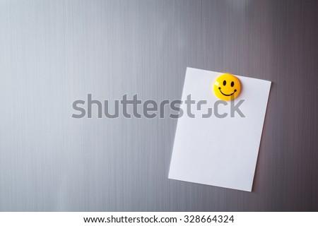 Empty paper sheet on refrigerator door - stock photo