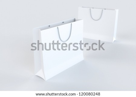 Empty Paper Shopping Bags on white surface - stock photo
