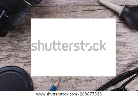 Empty paper with photographer stuff on wooden background
