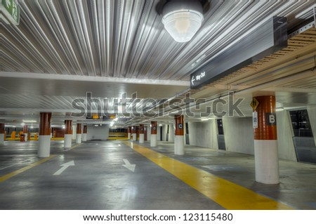 Empty parking interior at night, brightly lit, with red and white columns and yellow pedestrian walkway. - stock photo