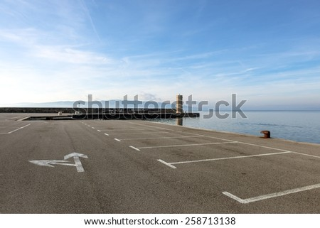 Empty parking lot at the sea under sky - stock photo