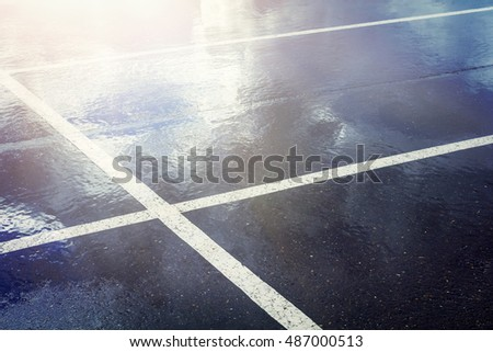 Empty parking lot with stripes . Wet concrete with reflection of blue sky with clouds