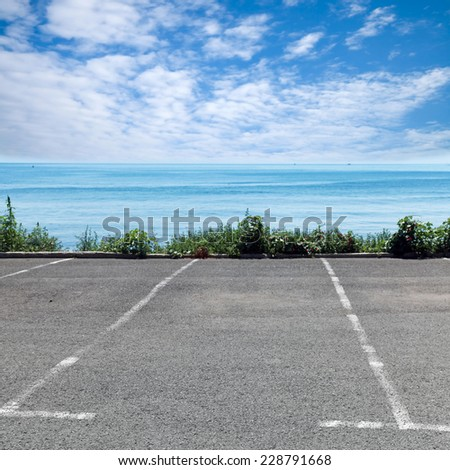 Empty parking place on the sea coast in summer day - stock photo