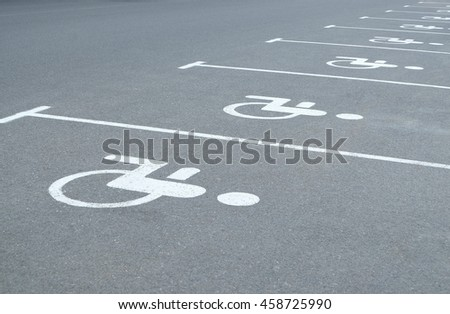 Empty parking places with handicapped or disabled signs on asphalt