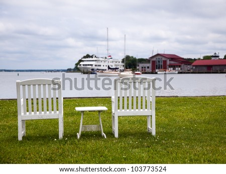 Empty patio chairs by side of the Chesapeake bay overlooking St Michaels harbor - stock photo