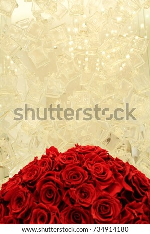 Empty perfume bottles and a bunch of red roses