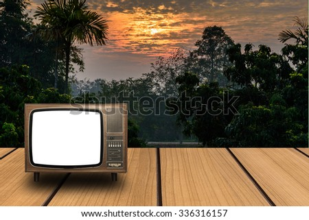 Empty perspective room with old television on wooden floor and sunset background