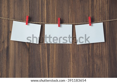 empty photo frames hanging with red clothespins on wooden background - stock photo