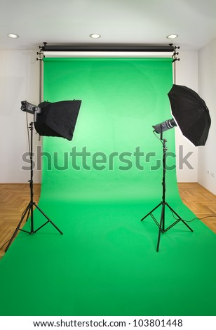 Empty Photo Studio with Lights and Green Backdrop - stock photo