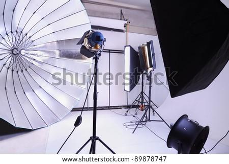 Empty photo studio with many modern lighting equipment; white backgrounds - stock photo