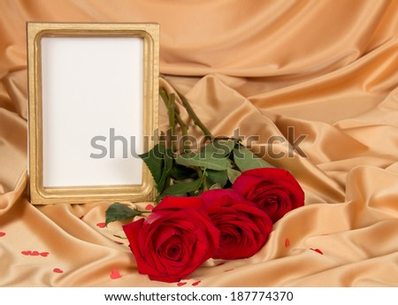 Empty photoframe with a bouquet of red roses on gold fabric - stock photo