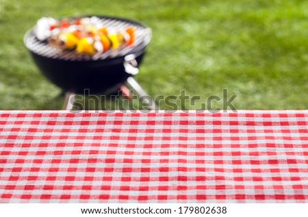 Empty picnic table background covered in a fresh country red and white checked cloth for your product placement or advertising with a barbecue on a green lawn behind - stock photo