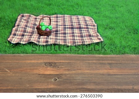 Empty Picnic Table Close-Up Blanket With Basket On The Fuzzy Background. Summer Picnic Scene And Concept - stock photo
