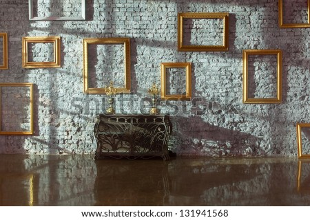 Empty picture frames on the brick wall and forged chest with candlesticks, side light. - stock photo