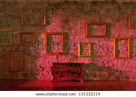 Empty picture frames on the brick wall and forged chest with candlesticks, side red light. - stock photo