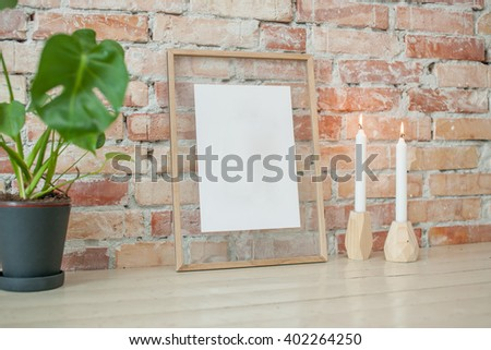 Empty picture in wooden frame where you can write your text, hanging on brick wall
