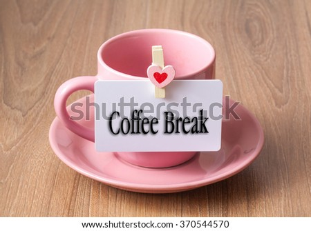 Empty pink color of coffee cup with wood clip heart shape and card - coffee break - stock photo