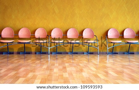 Empty pink plastic chairs in a row on yellow wall
