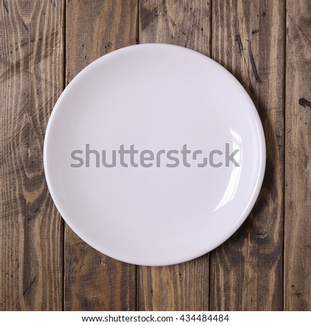 Empty, plain dinner dish on a rustic wooden table top background - stock photo