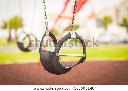 Empty plastic swing on the modern kids playground - stock photo