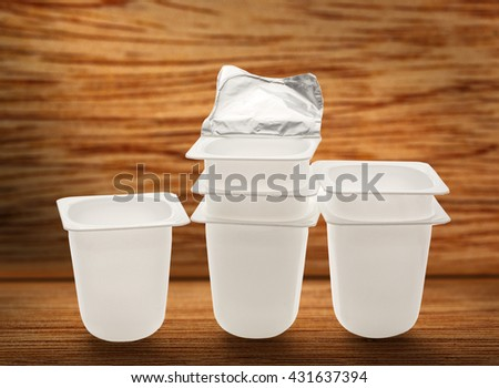 Empty plastic yogurt pots on wooden background