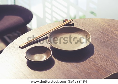 Empty plate and chopsticks on wood table,Japanese restaurant. - stock photo