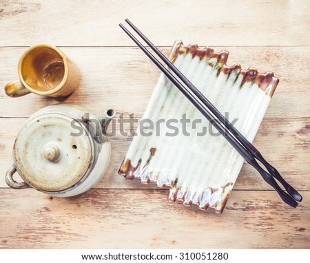 Empty plate and chopsticks, tea pot on wooden table - stock photo