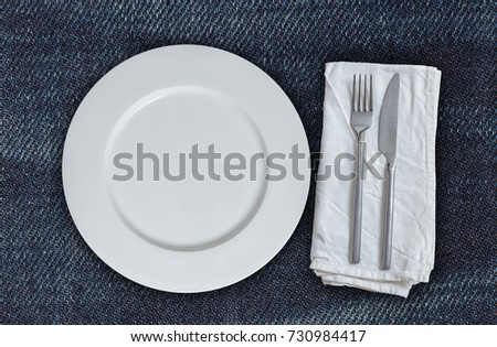 Empty plate and cutlery on jeans fabric.