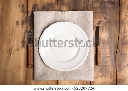 Empty Plate And Cutlery On The Wooden Table