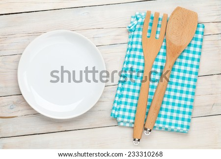 Empty plate and kitchen utensil over white wooden table background. View from above - stock photo