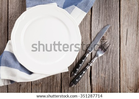 Empty plate and silverware on wooden table. Top view - stock photo