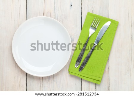 Empty plate and silverware over white wooden table background. View from above - stock photo