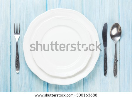 Empty plate and silverware over wooden table background. View from above with copy space