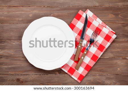 Empty plate and silverware over wooden table background. View from above with copy space - stock photo