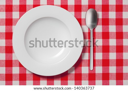 empty plate and spoon on red and white checkered tablecloth