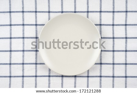 Empty plate at classic checkered tablecloth - stock photo