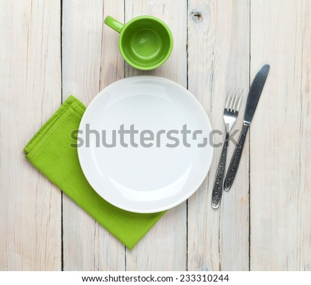 Empty plate, cup and silverware over white wooden table background. View from above - stock photo