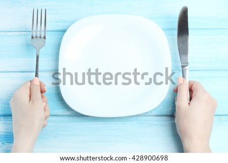 empty plate cutlery in hands table wood background gentle blue tone - stock photo