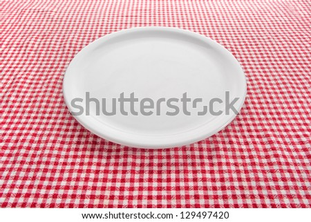 Empty plate. Empty white plate on kitchen table covered with checkered tablecloth. - stock photo