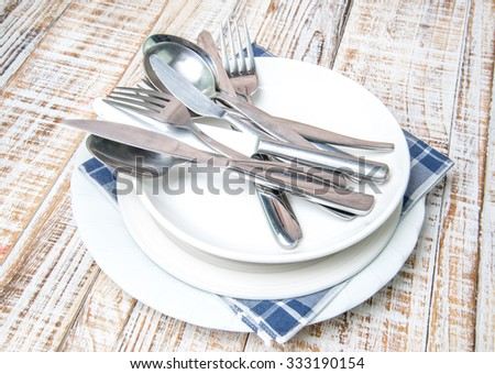 Empty plate, fork and table knife on old wooden background.