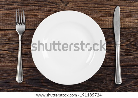 Empty plate, fork and table knife on old wooden background. Top view - stock photo