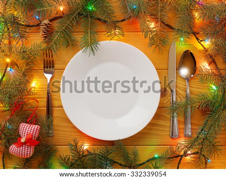 Empty Plate, fork, knife and spoon on wooden table. Christmas background - stock photo