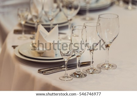 Empty plate, glasses and silverware set on white table