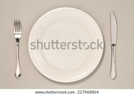 Empty Plate, Knife and Fork isolated on Grey Background with Real Shadow. Top View