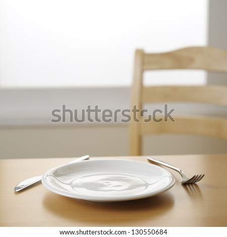 empty plate knife and fork on the table - stock photo