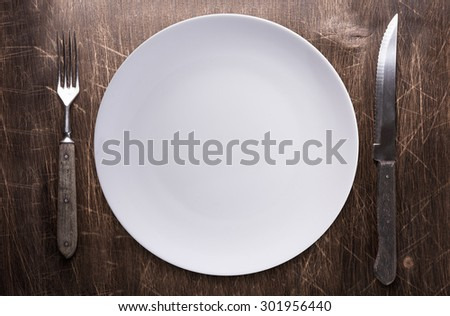 Empty plate, knife and fork over wooden table background. View from top with copy space. - stock photo