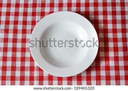 empty plate on a red and white tablecloth - stock photo