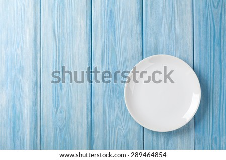 Empty plate on blue wooden background. Top view with copy space - stock photo