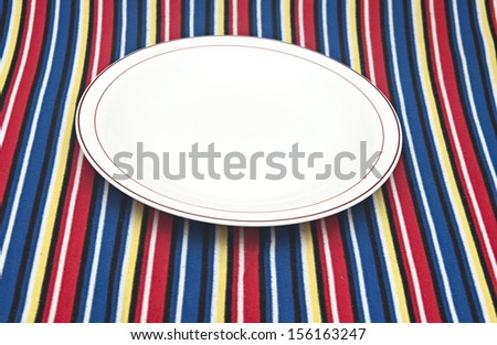 Empty plate on colorful tablecloth