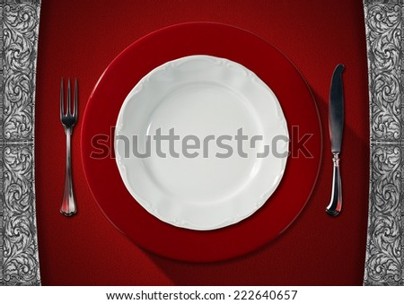 Empty Plate on Red Velvet Background / Empty and white plate on red under plate with silver cutlery, fork and knife on red velvet background with silver floral decorations